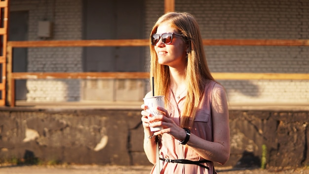 Young woman with a cup of lemonade outside sunny day and urban food court