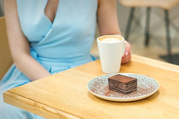 屋外のカフェのテーブルに座っているコーヒーとケーキのかけらを持つ若い女性