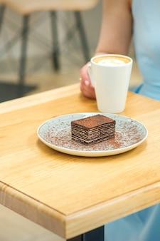 Молодая женщина с чашкой кофе и куском торта, сидя за столом в кафе на открытом воздухе
