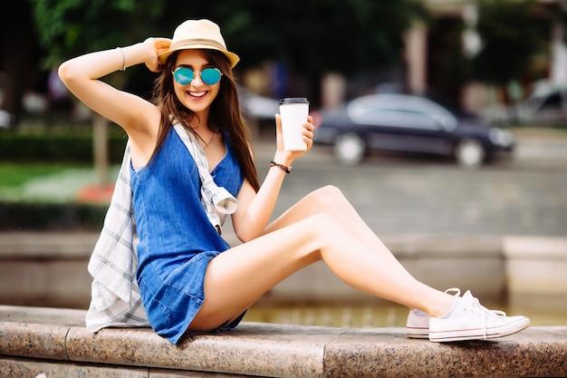분수 근처 커피 한잔과 함께 젊은 여성