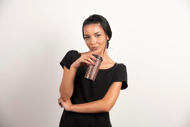 白い壁にコーヒーのカップを持つ若い女性。
