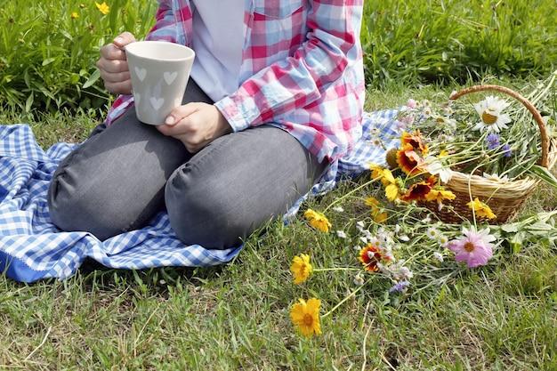 Молодая женщина с чашкой кофе, сидя на лугу на открытом воздухе
