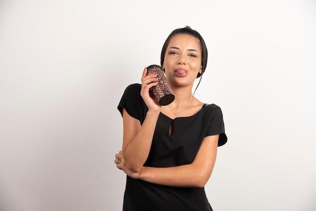 白い壁に立っているコーヒーのカップを持つ若い女性。