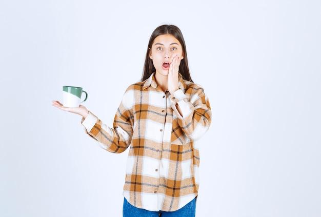 一杯のコーヒーを持つ若い女性は何かに驚いた。
