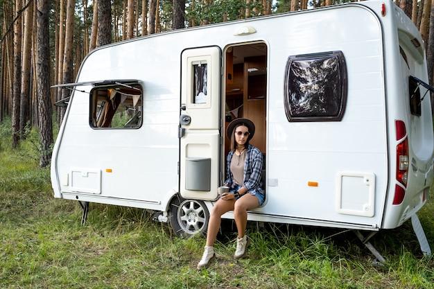 夏の旅行中にトレーラーハウスの開いたドアに座っているお茶のカップを持つ若い女性
