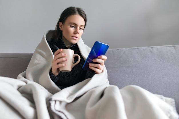 Молодая женщина с чашкой, смартфоном, сидя дома на диване под теплым флисовым одеялом, копией пространства