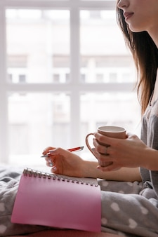 Young woman with cup of tea makes notes in writing book.