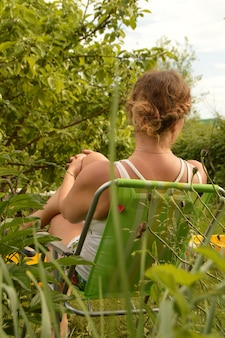 A young woman with curly blonde hair in a white t-shirt resting in a chair in the garden