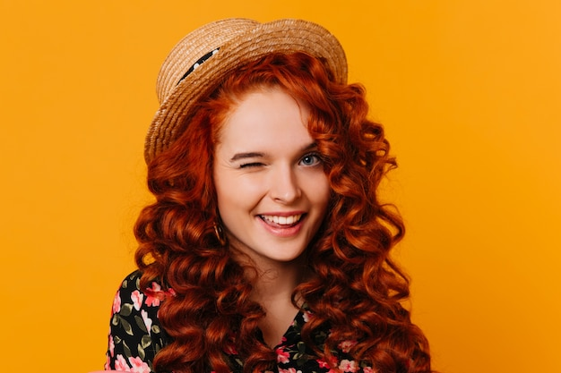 Young woman with curly bright hair and blue eyes in good mood winks, posing in hat on orange space.