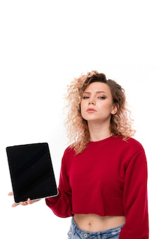 Young woman with curly fair hair holds a tablet