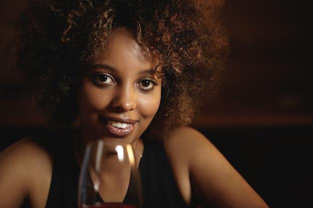 巻き毛と赤ワインのグラスを持つ若い女性