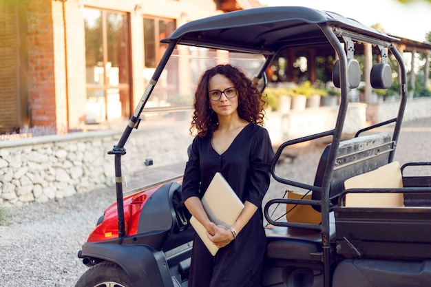Young woman with curly hair in black dress holding in hands a laptope, poses near vehicle and smiling.