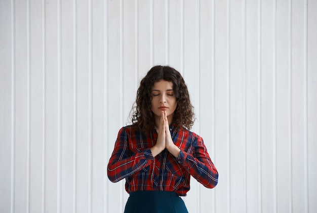 Young woman with curly hair and checkered shirt praying