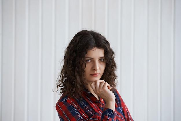 Giovane donna con capelli ricci e camicia a scacchi