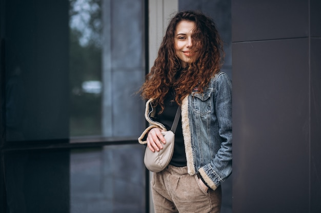 Young woman with curly hair in denim jacket