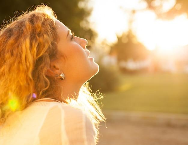 巻き毛を持つ若い女性は、晴れた日楽しんで
