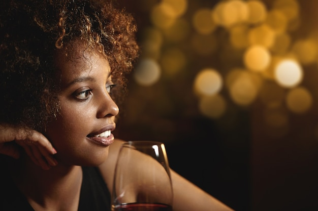 Young woman with curly hair and a glass of red wine