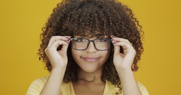 彼女の眼鏡に満足している巻き毛の若い女性。アイケアのコンセプト。