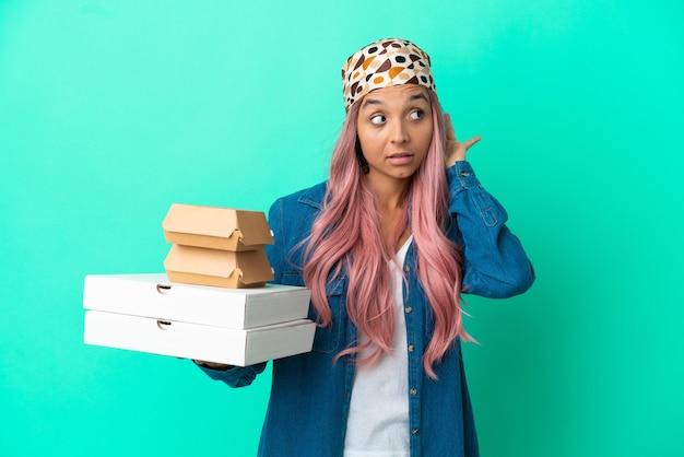 孤立したピンクの背景の上に計量機を保持している巻き毛の若い女性