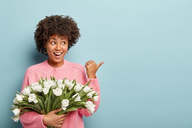 흰 꽃의 꽃다발을 들고 곱슬 머리를 가진 젊은 여자