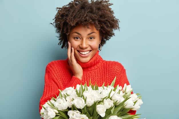白い花の花束を保持している巻き毛の若い女性