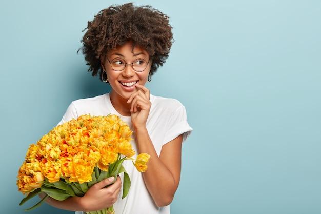 Молодая женщина с вьющимися волосами держит букет желтых цветов