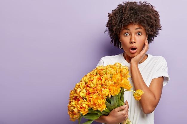 노란색 꽃의 꽃다발을 들고 곱슬 머리를 가진 젊은 여자
