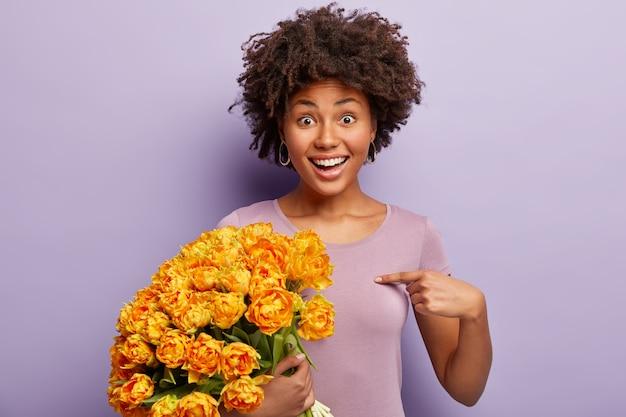黄色い花の花束を保持している巻き毛の若い女性