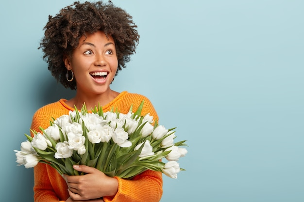 Young woman with curly hair holding bouquet of white flowers