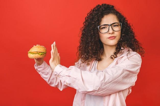 ハンバーガーを保持している巻き毛を持つ若い女