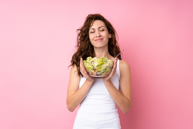 Young woman with curly hair holding a salad over isolated pink
