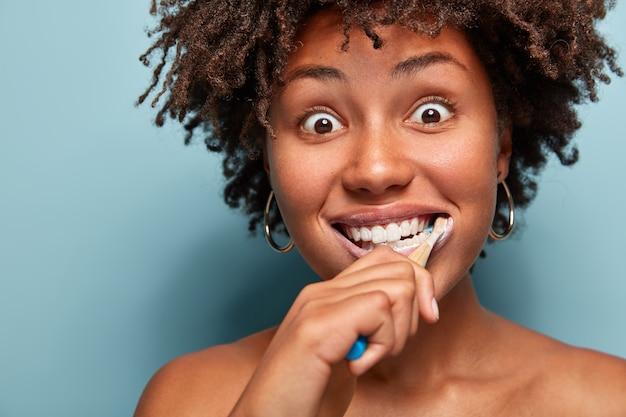歯ブラシを保持している巻き毛の若い女性