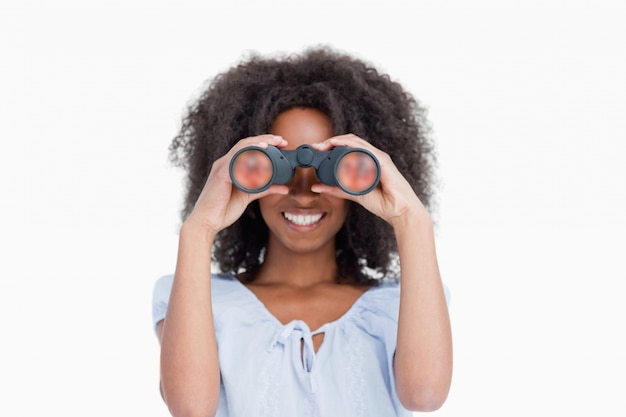 Young woman with curly hair looking through binoculars