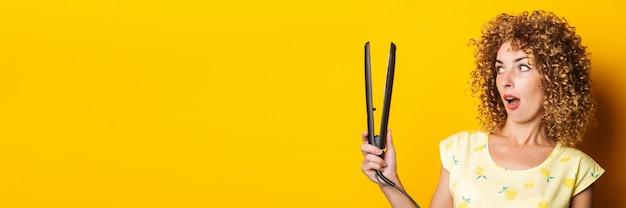巻き毛の若い女性は、黄色の背景のストレートヘアアイロンに驚いて見えます。