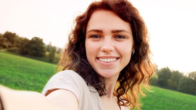 Молодая женщина с вьющимися волосами делает селфи на закате на фоне красивого летнего пейзажа.