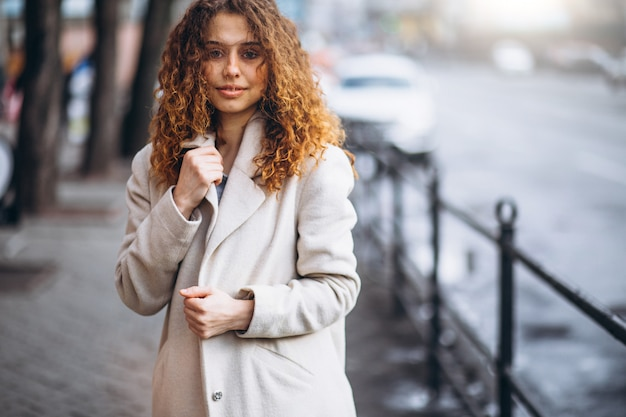 Young woman with curly hair outside the street