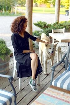 Молодая женщина с вьющимися волосами играет с собакой акита-ину