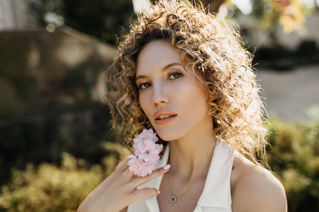 ピンクの花と屋外でポーズをとって巻き毛の若い女性