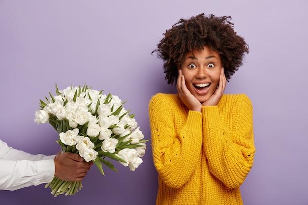 Молодая женщина с вьющимися волосами получает букет белых цветов