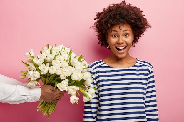 Giovane donna con capelli ricci che riceve bouquet di fiori bianchi