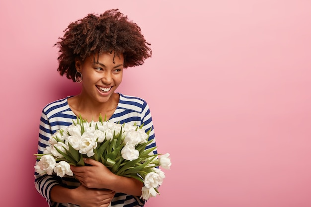 Young woman with curly hair receiving bouquet of white flowers