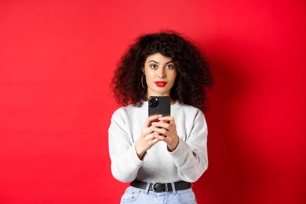 Giovane donna con i capelli ricci, che registra video su smartphone, scatta foto sul cellulare e guarda la telecamera, in piedi su sfondo rosso.
