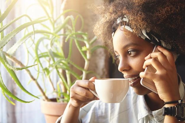 카페에 앉아 곱슬 머리를 가진 젊은 여자
