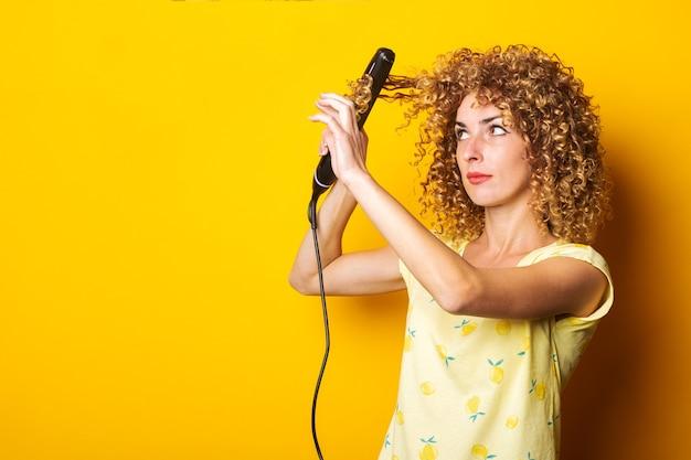 巻き毛の若い女性は、黄色の背景にストレートヘアアイロンを持って、髪をまっすぐにします。