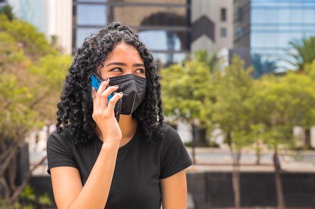 電話で話している巻き毛の若い女性、彼女は黒いマスクを身に着けています