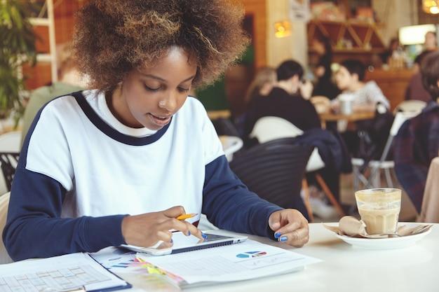 カフェでタブレットを使用して巻き毛の若い女性