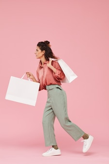 Young woman with curly hair walking with big paper bags against the pink background