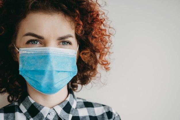 空きスペースのある白いスタジオの背景に医療マスクを身に着けている巻き毛の若い女性