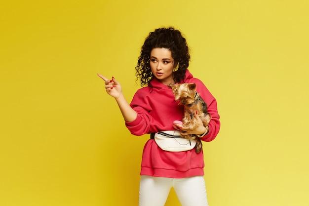 ピンクのパーカーを着た巻き毛の若い女性が、小さなかわいい犬を手に持ち、分離された黄色の背景に指を脇に向けている