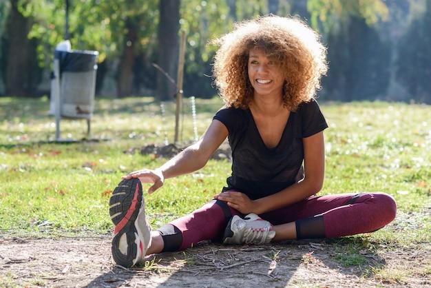 Giovane donna con i capelli ricci allenarsi nel pomeriggio